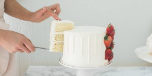 Getting a sliced piece of vanilla cake with strawberries on the side